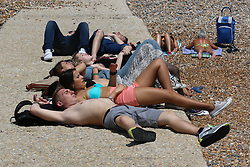 © Licensed to London News Pictures.21/06/2014. Brighton, UK. A group of people sunbathing on Brighton beach. Thousands of people are taking a weekend away to the South Coast with temperatures reaching 25C. Photo credit : Hugo Michiels/LNP