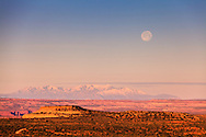 The full moon sets at sunrise over Utah's Canyonlands National Park and the Green River plateau, with Mount Pennell and Capitol Reef National Park in the distant background.<br />