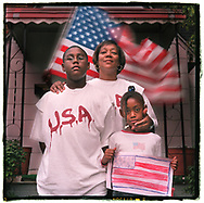 "Darlene Marion (center), age 45, outside her Pontiac, Michigan, home with son Darius Fowlkes (left), age 12, and daughter Taylor Fowlkes (right), age 7, with a flag she drew.  Darlene Marion wrote to her children ""America is a great country and its ours, we don't want anyone to take our freedom away."""