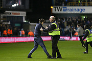 Millwall fan is caught by steward after running on the pitch during the The FA Cup fourth round match between Millwall and Everton at The Den, London, England on 26 January 2019.