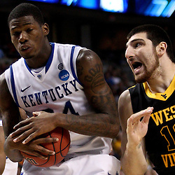 Mar 19, 2011; Tampa, FL, USA; Kentucky Wildcats guard DeAndre Liggins (34) rebounds a ball over West Virginia Mountaineers forward Deniz Kilicli (13) during the first half  of the third round of the 2011 NCAA men's basketball tournament at the St. Pete Times Forum.  Mandatory Credit: Derick E. Hingle