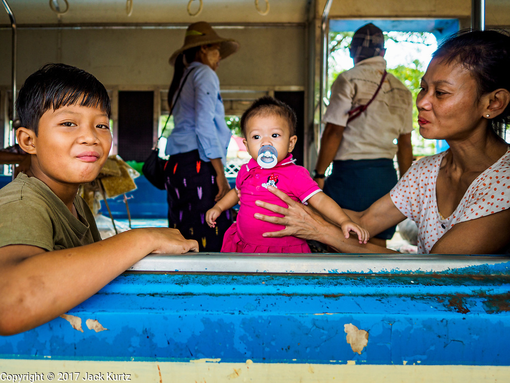 25 NOVEMBER 2017 - YANGON, MYANMAR: A family on the Yangon Circular Train in Danyingon station, in the middle of the train's loop. The Yangon Circular Train is a 45.9-kilometre (28.5 mi) 39-station two track loop system connects satellite towns and suburban areas to downtown. The train was built during the British colonial period, the second track was built in 1954. Trains currently run both directions (clockwise and counter-clockwise) around the city. The trains are the least expensive way to get across Yangon and they are very popular with Yangon's working class. About 100,000 people ride the train every day. A a ticket costs 200 Kyat (about .17¢ US) for the entire 28.5 mile loop.    PHOTO BY JACK KURTZ