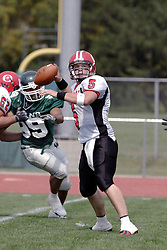 09 September 2006  Comet Quarterback Calvin McNamara set for a throw while the Titans clamor in from behind..In the first ever football competition between the Olivet Comets and the Illinois Wesleyan Titans, the Titans strut off the field with a 21- 6 victory. .Game action took place at Wilder Field on the campus of Illinois Wesleyan University in Bloomington Illinois.