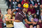 Uche Ikpeazu (#19) of Heart of Midlothian FC wins a header against Andy Considine (#4) of Aberdeen FC during the Betfred Scottish Football League Cup quarter final match between Heart of Midlothian FC and Aberdeen FC at Tynecastle Stadium, Edinburgh, Scotland on 25 September 2019.