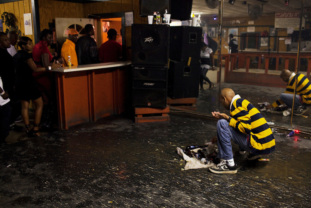 """A worker at Scruples Sports Bar cleans up the pile of burnt money, beer bottles and the t-shirt commemorating the life and death of Demetrius """"Butta"""" Anderson, 18, the night after his funeral in the  Baptist Town neighborhood of Greenwood, Mississippi on Friday, November 5, 2010. After the funeral and burial a block party ensued, where the town residents celebrated Butta's life. Late that night many of his friends and some family gathered at Scruples, a club down the highway in Itta Bena, Mississippi and danced and drank until the bar closed."""