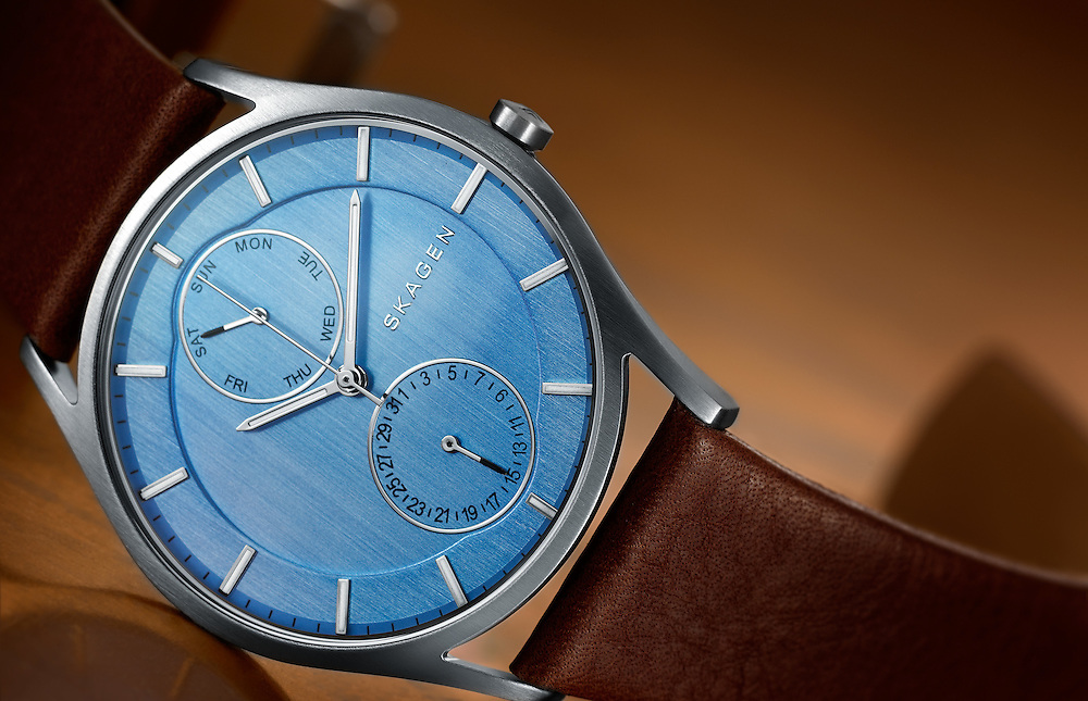 Skagen watch with blue face lying on it's side on a sheet of copper.