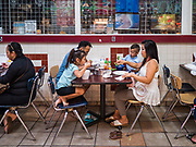 03 AUGUST 2019 - ST. PAUL, MINNESOTA: A family has lunch in the food court at the Hmong Village shopping center. Thousands of Hmong people, originally from the mountains of central Laos, settled in the Twin Cities in the late 1970s and early 1980s. Most were refugees displaced by the American war in Southeast Asia. According to the 2010 U.S. Census, there are now 66,000 ethnic Hmong in the Minneapolis-St. Paul area, making it the largest urban Hmong population in the world. There are two large Hmong markers in St. Paul. The Hmongtown Marketplace has are more than 125 shops, 11 restaurants, and a farmers' market in the summer. Hmong Village is newer and has more than 250 shops and 17 restaurants.    PHOTO BY JACK KURTZ