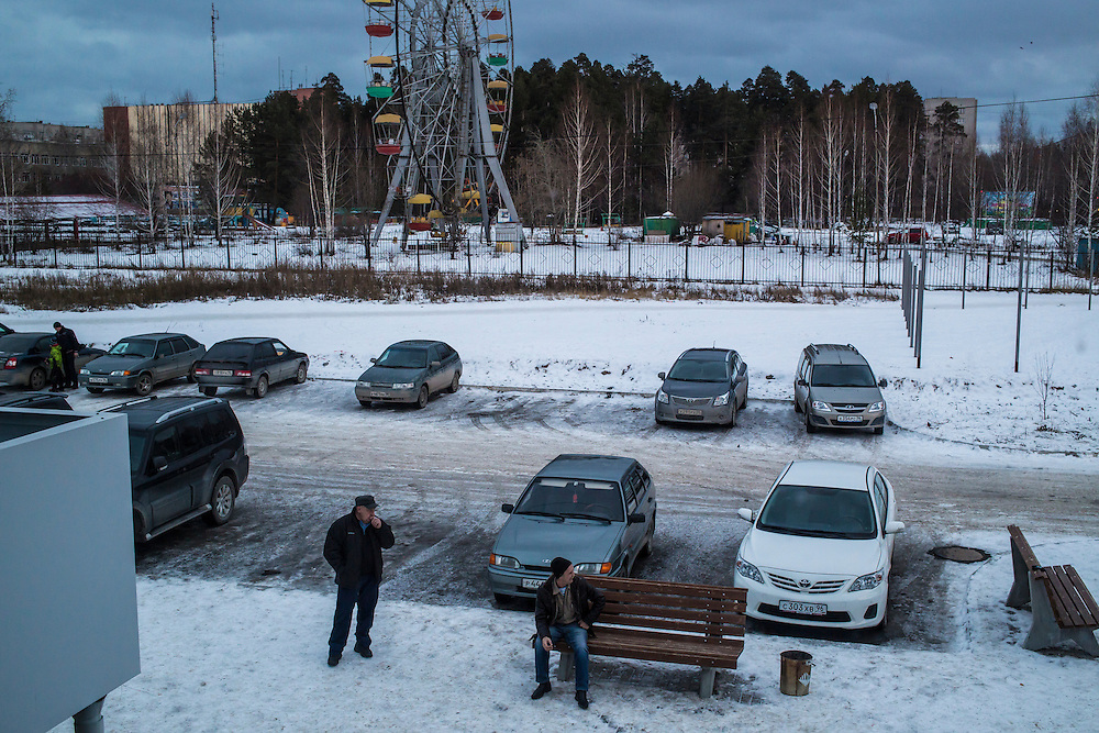 Men sit outside to smoke cigarettes on Saturday, November 30, 2013 in Asbest, Russia.