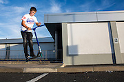 A Wadebridge youngster scootering in Lidl car park. WREN community energy has given funding received from the Feed in tariff from their solar array to a project that build a local skate park within the town. Wadebridge, Cornwall. UK
