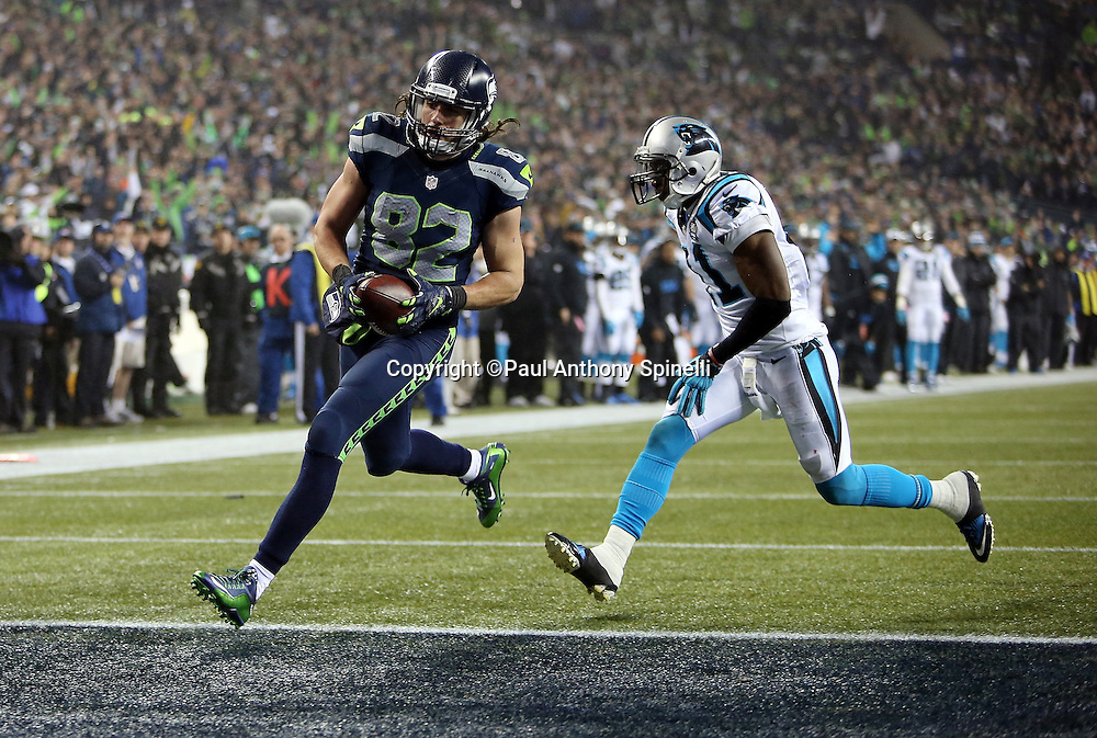 Seattle Seahawks tight end Luke Willson (82) catches a 25 yard fourth quarter touchdown pass for a 24-10 Seahawks lead while covered by Carolina Panthers strong safety Roman Harper (41) during the NFL week 19 NFC Divisional Playoff football game against the Carolina Panthers on Saturday, Jan. 10, 2015 in Seattle. The Seahawks won the game 31-17. ©Paul Anthony Spinelli