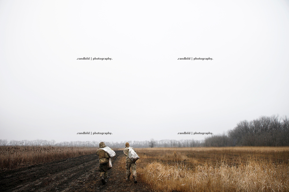 Charlie and Cowboy (le. to ri.) carry bags full of wet firewood over an open field into their trench position.<br /> <br /> Fascinated by war and convinced of a simple shaped nationalistic ideology, five vonuteer warriors from Europe and USA left behind their former lifes. Walking into battle in Ukraine, Ben, Alex, Craig, Charlie and Cowboy made it to the frontline and joint the right-wing militia Right Sector, supporting the ukrainian army which is short of staff. Receiving no payments but shelter, food and ammo the foreigners selfmade battlegroup Task Force Pluto is a loose union of individuals and no particular ukrainian phenomenon. The Boom Stick Brotherhood would move on to another conflict around the globe when Ukraine become boring to them. They want to be involved in battle. That&acute;s what they are aiming for. Living a dream of smoking guns, camaraderie and outdoor life. An extreme lifestyle devoted to an everyday look into the face of death.<br /> <br /> The Boom Stick Brotherhood is a multi-national, multi-religious and multi-ethnic group:<br /> Ben, an austrian infantryman travelling hot zones since years. Bored by his own reluctant national army at home he made plenty of experience in Kosovo, Syria, Iraq and Ukraine.<br /> Alex, Ben&acute;s brother in arms from austrian army times deserted and fled the country to get ultimately involed in frontline fights.<br /> Craig was fighting almost 6 years for the US-Army in Iraq and Afghanistan but got in conflict with the law afterwards. He escaped conviction by going abroad.<br /> Charlie was totally bored by his californian routine in Silicon Valley but failed to join the US-Army and French Foreign Legion. Eventually he found battle opportunities in Ukraine.<br /> Petty crook Cowboy got in trouble with US law only days before his Army unit was to deployed to Afghanistan. Later during a day release he made it from prison to France but French Foreign Legion rejected him. He gave Ukraine a go.