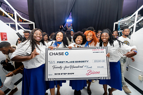 Members of Zeta Phi Beta sorority, the winning Greek Step Show team, holding a large check for twenty-five hundred dollars.