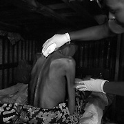 Home basec are provider Sarah Kilonzo bathes HIV patient Sophia Konyo at her home in the Kariobangi slums of Nairobi. Sophia is very weak an unable to care for herself.