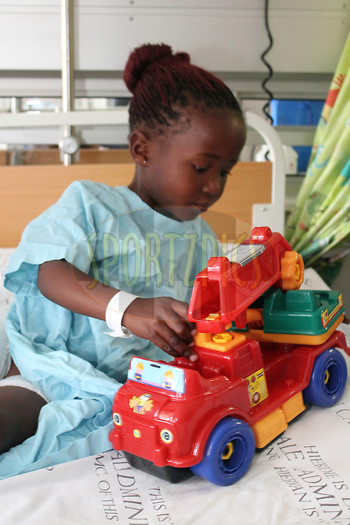 One of the young burn victims playing with the toys during the visit to the Red Cross War Memorial Children's Hospital by the Engen Motor Racing drivers on the 20th September 2012. Photo by Jacques Rossouw/SPORTZPICS