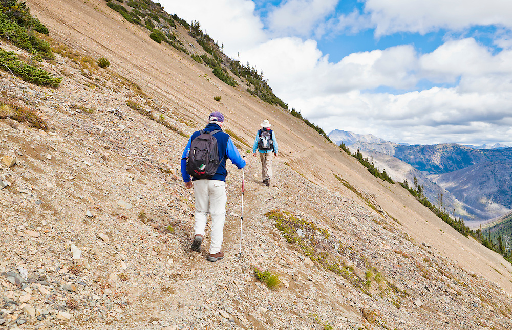 Two men walking along a mountainside on a narrow trail.  Pacific Crest Trail, North Cascades of Washington, USA.