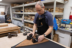 A pattern is laid out and weighted down before an umbrella's cover is cut. Craftspeople at Fox Umbrellas Ltd, a company in Croydon, Surrey, that has been going for over 150 years hand build quality umbrellas. Croydon, Surrey, March 06 2019.