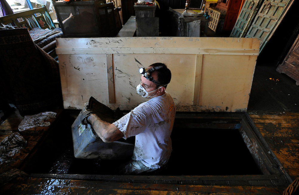 Jude Fitzgerald salvages items from a mud filled basement two days after Tropical Storm Irene, in Brattleboro, Vt., Tuesday, Aug. 30, 2011.  (AP Photo/Jessica Hill)