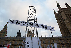 © licensed to London News Pictures. London, UK 01/12/2012. Protesters erect a 7.2 metre high fake ?fracking rig? outside parliament to protest against the expansion of hydraulic fracturing for shale gas into the UK Photo credit: Tolga Akmen/LNP