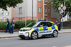 © Licensed to London News Pictures. 27/05/2019. London, UK.  Police search teams walk past a police car at the crime scene in St Paul's Way, Mile End in Tower Hamlets, where a 23 year old man was stabbed multiple times yesterday, 26th May and died overnight in hospital.  Photo credit: Vickie Flores/LNP