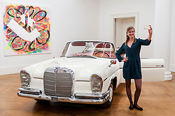 © Licensed to London News Pictures. 12/08/2016. London, UK. A Sotheby's employee takes a selfie with James Mason's Mercedes-Benz 300 SE Cabriolet, purchased from new by the great British actor (est. GBP 150,000 - 250,000), at the photocall for classic cars at Sotheby's, New Bond Street, ahead of their auction on 7 September in Battersea Park. Photo credit : Stephen Chung/LNP