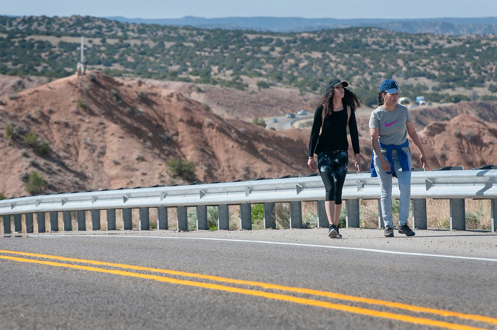 em041317e/jnorth/Yulissa Morales, left, and Azucena Castillo, from Santa Fe, walks along Juan Madina Road making their way to the Santuario de Chimayo Thursday April 13, 2017. Hundreds of people were making their pilgrimage to the Northern New Mexico church on Thursday, thousands will on Good Friday.   (Eddie Moore/Albuquerque Journal