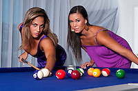 2 young womans playing pool looking at camera very sensual.