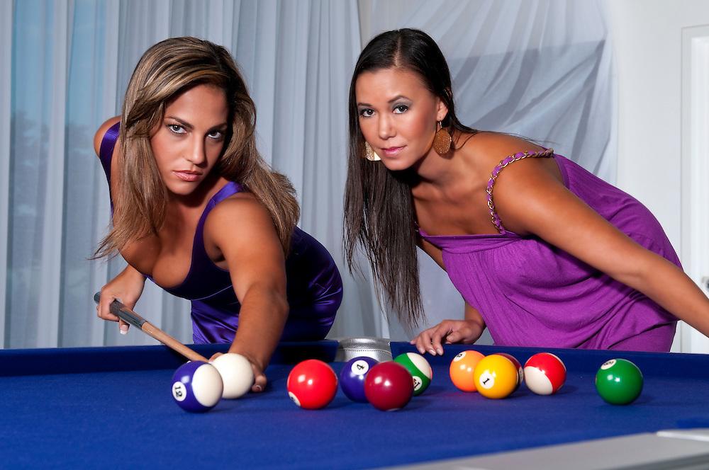 2 young womans playing pool looking at camera very sensual.