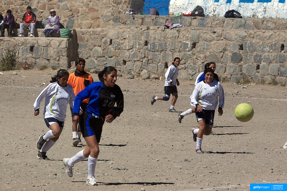'Attitude at Altitude' Football in Potosi, Bolivia'..Girls play football during the Liga Deportiva San Cristobal finals matches on the stone and gravel surface high in the hills over Potosi. Potosi, Bolivia 9th May 2010...'Attitude at Altitude' Football in Potosi, Bolivia'..The Calvario players greet the final whistle with joyous celebration, high fives and bear hugs the players are sprayed with local Potosina beer after a monumental 3-1 victory over arch rivals Galpes S.C. in the Liga Deportiva San Cristobal. The Cup Final, high in the hills over Potosi. Bolivia, is a scene familiar to many small local football leagues around the world, only this time the game isn't played on grass but a rock hard earth pitch amongst gravel and boulders and white lines that are as straight as a witches nose, The hard surface resembles the earth from Cerro Rico the huge mountain that overlooks the town. .. Sitting at 4,090M (13,420 Feet) above sea level the small mining community of Potosi, Bolivia is one of the highest cities in the world by elevation and sits 'sky high' in the hills of the land locked nation. ..Overlooking the city is the infamous mountain, Cerro Rico (rich mountain), a mountain conceived to be made of silver ore. It was the major supplier of silver for the spanish empire and has been mined since 1546, according to records 45,000 tons of pure silver were mined from Cerro Rico between 1556 and 1783, 9000 tons of which went to the Spanish Monarchy. The mountain produced fabulous wealth and became one of the largest and wealthiest cities in Latin America. The Extraordinary riches of Potosi were featured in Maguel de Cervantes famous novel 'Don Quixote'. One theory holds that the mint mark of Potosi, the letters PTSI superimposed on one another is the origin of the dollar sign...Today mainly zinc, lead, tin and small quantities of silver are extracted from the mine by over 100 co operatives and private mining companies who still mine the mountain in poor working condi