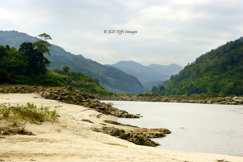 View up the Mekong River somewhere in Laos.  Sandy river bank, colorless river water, and distand hills.