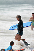 MANHATTAN BEACH, CALIFORNIA, USA - JULY 1, 2013. A senior surfer enters the water on July 1, 2013. People flocked to the beach to avoid dangerous high temperatures inland.