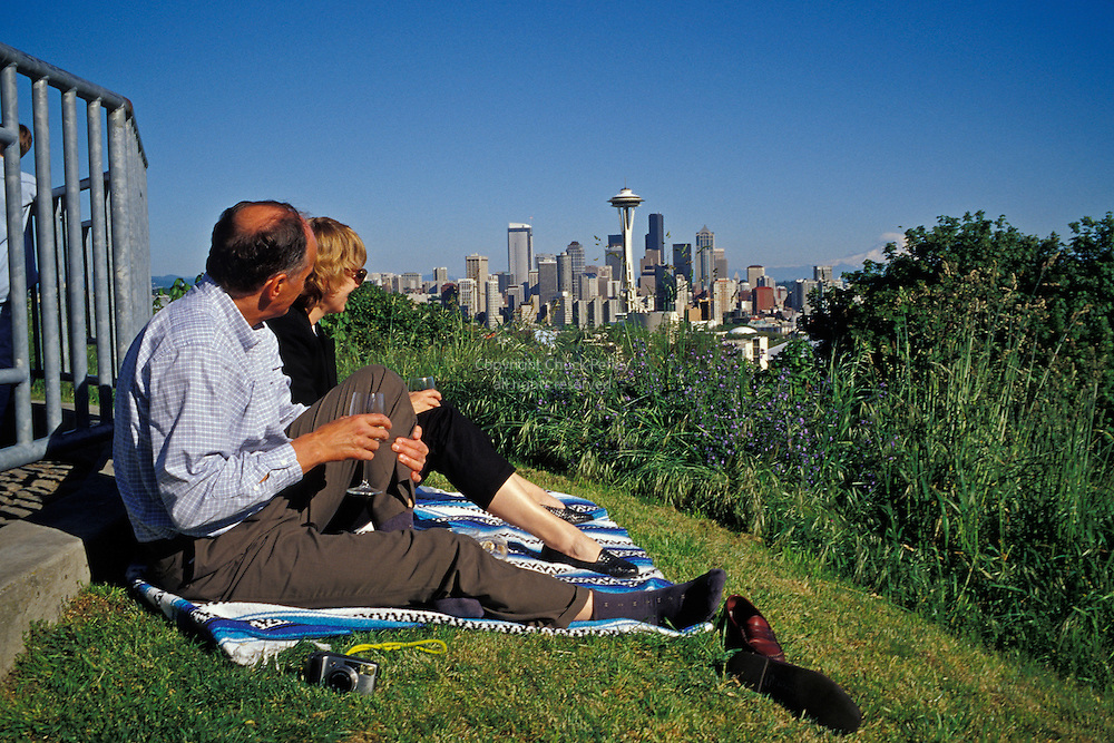Man and woman picnic at Kerry Park with Seattle Washington skyline in background<br />