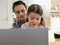 Girl (3-6) using laptop with father at home