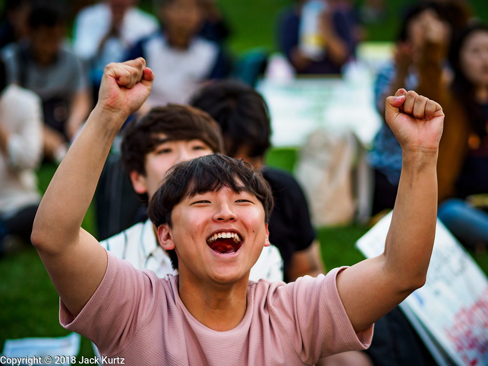 """15 JUNE 2018 - SEOUL, SOUTH KOREA: A South Korean teenager cheers during a rally to mark the anniversary of the signing of the June 15th North–South Joint Declaration between South Korea and North Korea. The Declaration was negotiated by late South Korean President Kim Dae-jung and North Korean leader Kim Jong-il and signed on 15 June 2000. It was a part of South Korea's """"Sunshine Policy,"""" which guides the South's relationship with North Korea. This year's observance of the anniversary was bolstered by the recent thawing in relations between North Korea and South Korea and the US.   PHOTO BY JACK KURTZ"""