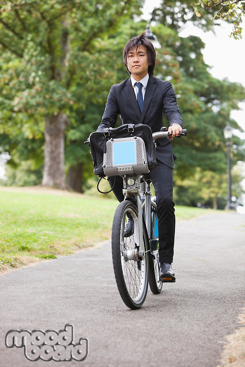 Portrait of young businessman commuting by his bicycle