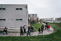 "NAPLES, ITALY - 16 MARCH 2018: Teenagers followed by their instructors walk out of the gym after practicing parkour at ""Il Tappeto di Iqbal"" (Iqbal's carpet), a non-profit cooperative in Barra, the estern district of Naples, Italy, on March 16th 2018.<br /> <br /> Il Tappeto di Iqbal (Iqbal's Carpet) is a non-profit cooperative founded in 2015 and Save The Children partner since 2015 that operates in the Naple's eastern neighborhood of Barra children in the arts of circus, theater and parkour. It was named after Iqbal Masih, a Pakistani boy who escaped from life as a child slave and became an activist against bonded labor in the 1990s.<br /> Barra, which is home to some 45,000 people, has the highest rate of school dropouts in the Italian region of Campania. Once a thriving industrial community, many of the factories were destroyed in a 1980 earthquake and never rebuilt. The resulting de-industrialization turned Barra into a poor, decaying neighborhood. There are no cinemas, theaters, parks or public spaces in Barra.<br /> The vast majority of children from poor families are faced with the choice of working in the black economy or joining the ranks of the organised crime.<br /> Recently, Save the Children Italy opened a number of educational and social spaces in Barra. The centers, known as Punti Luce, or points of light, aim to help local kids stay out of the ranks of the organised crime and have also become hubs for Iqbal's Carpet to work."