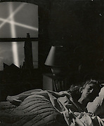 Woman asleep with search lights in window, 1940s