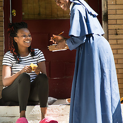 Teak Phillips | St. Louis Review | @TeakPhillips<br /> <br /> Sister Mary Paschal of the Society of the Mother of Peace went door-to-door in St. Augustine Parish in north St. Louis to proclaim the Gospel message. She met and prayed with Carlotta Williams, who lives in the 5300 block of Maple Avenue in the Visitation Park neighborhood.