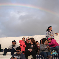 Marina Bond stands at the top of the bleachers framed by a rainbow to watch the car races at Uranium Capitol Speedway in Milan Saturday.