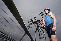 Cyclist carrying bicycle on foot bridge low angle view