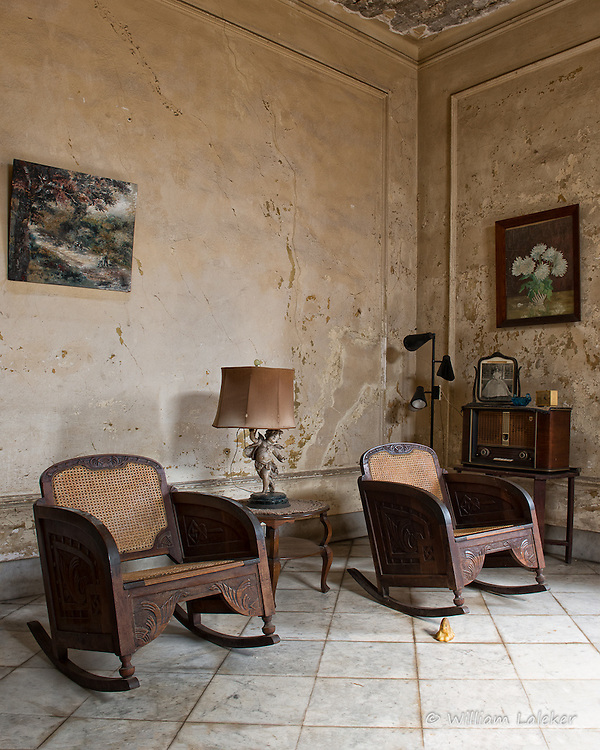 A pair of antique wood carved chairs and old radio in the  sitting room in a once glamorous home built in 1926.