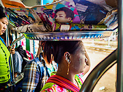 25 NOVEMBER 2017 - YANGON, MYANMAR: A food vendor stands in the doorway of the Yangon Circular Train as it pulls into a station. The Yangon Circular Train is a 45.9-kilometre (28.5 mi) 39-station two track loop system connects satellite towns and suburban areas to downtown. The train was built during the British colonial period, the second track was built in 1954. Trains currently run both directions (clockwise and counter-clockwise) around the city. The trains are the least expensive way to get across Yangon and they are very popular with Yangon's working class. About 100,000 people ride the train every day. A a ticket costs 200 Kyat (about .17¢ US) for the entire 28.5 mile loop.    PHOTO BY JACK KURTZ