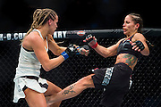 Liz Carmouche connects with a kick against Katlyn Chookagian during UFC 205 at Madison Square Garden in New York, New York on November 12, 2016.  (Cooper Neill for The Players Tribune)