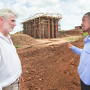 CAPTION: Through this technology, the brick making industry can shift from wood to biofuel, making it more environmentally friendly. This particular biofuel comes from the residues of the tobacco, rice and sugar industries. A quarter of the energy input is needed, helping to preserve Malawi's endangered forests while also emitting just a quater of the amount of carbon dioxide into the atmosphere. Here, Eco-Bricks Project Officer Titus Malunga discusses landscaping with Technical Advisor Peter Schramm at the vertical shaft brick kiln site near Lilongwe. LOCATION: Eco-Bricks (Mthyoka), Lilongwe, Malawi. INDIVIDUAL(S) PHOTOGRAPHED: Peter Schramm (left) and Titus Malunga (right).