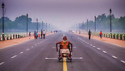 """16th October 2015, Delhi, India. A man travels in a wheelchair down the centre of Raj Path in Delhi, India on the 16th October 2015.<br /> <br /> Rajpath (meaning """"King's Way"""") is the ceremonial boulevard in New Delhi, India, that runs from Rashtrapati Bhavan on Raisina Hill through Vijay Chowk and India Gate to National Stadium, Delhi. The avenue is lined on both sides by huge lawns, canals and rows of trees. Considered to be one of the most important roads in India, it is where the annual Republic Day parade takes place on 26 January. Janpath (meaning """"People's Way"""") crosses the road. Rajpath runs in east-west direction. Roads from Connaught Place, the financial centre of Delhi, run into Rajpath from north<br /> <br /> PHOTOGRAPH BY AND COPYRIGHT OF SIMON DE TREY-WHITE a photographer in Delhi<br /> <br /> + 91 98103 99809<br /> email: simon@simondetreywhite.com"""
