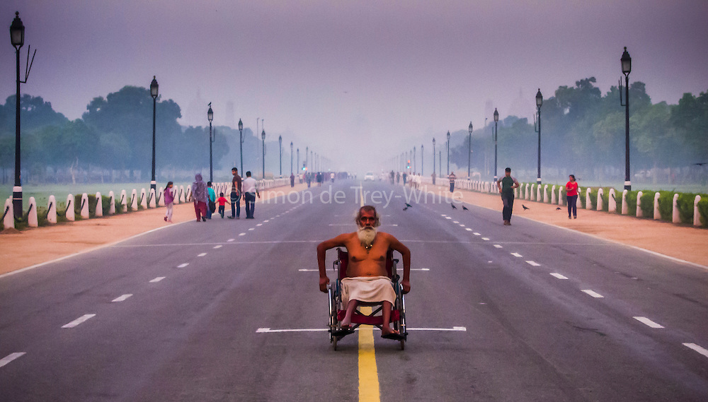 16th October 2015, Delhi, India. A man travels in a wheelchair down the centre of Raj Path in Delhi, India on the 16th October 2015.<br /> <br /> Rajpath (meaning &quot;King's Way&quot;) is the ceremonial boulevard in New Delhi, India, that runs from Rashtrapati Bhavan on Raisina Hill through Vijay Chowk and India Gate to National Stadium, Delhi. The avenue is lined on both sides by huge lawns, canals and rows of trees. Considered to be one of the most important roads in India, it is where the annual Republic Day parade takes place on 26 January. Janpath (meaning &quot;People's Way&quot;) crosses the road. Rajpath runs in east-west direction. Roads from Connaught Place, the financial centre of Delhi, run into Rajpath from north<br /> <br /> PHOTOGRAPH BY AND COPYRIGHT OF SIMON DE TREY-WHITE a photographer in Delhi<br /> <br /> + 91 98103 99809<br /> email: simon@simondetreywhite.com