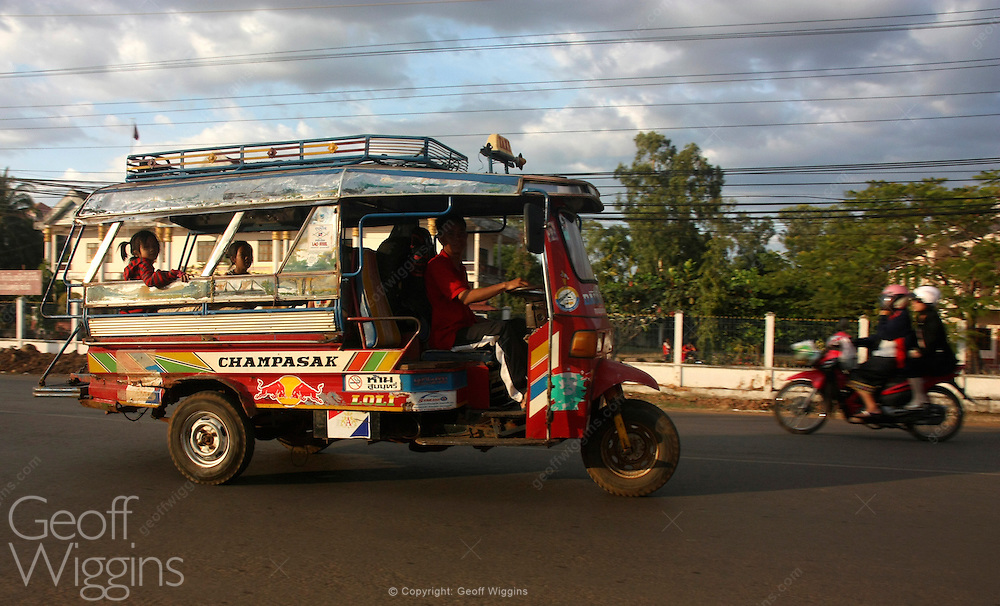 Laotian tricycle motor rickshaw bus rushes through city streets of Pakse Lao