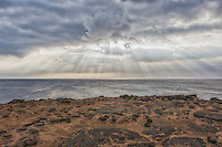 Rays of light through the clouds on the ocean on the South Point of the big island of Hawaii.  Volcanic beach and grasses in the foreground.