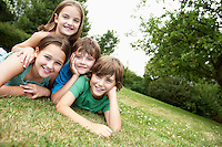 Two young girls and boys lying in park together portrait