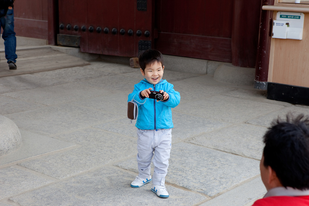 Boy taking photographs at  the main palace gate at Gwanghwamun of Gyeongbokgung Palace, the main royal palace of Joseon Dynasty. / Seoul, South Korea, Republic of Korea, KOR, 25 April 2010.
