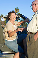 Senior woman getting out of car, senior man holding woman's hand